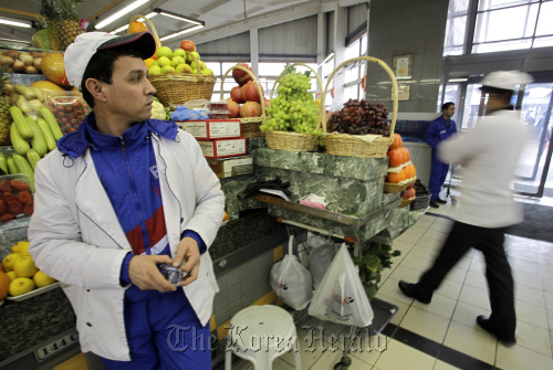 A trader stands by the fruit stall waiting for customers at the Dorogomilovsky food market in Moscow. (Bloomberg)