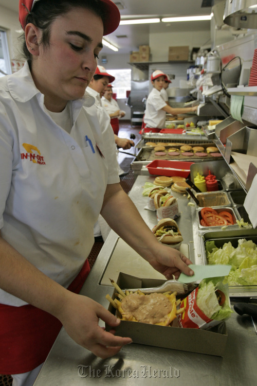 A staff prepares burgers for lunch customers at In-N-Out Burger in San Marcos, California. (MCT)