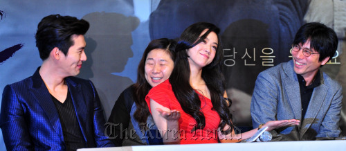 "Chinese actress Tang Wei (center) shrugs at a press conference for ""Late Autumn"" with her Korean co-star Hyun Bin (left) and director Kim Tae-yong (right). (Kim Myung-sub/The Korea Herald)"