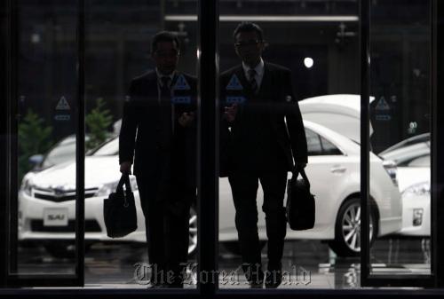 Men exit Toyota Motor Corp.'s Tokyo headquarters. (Bloomberg)