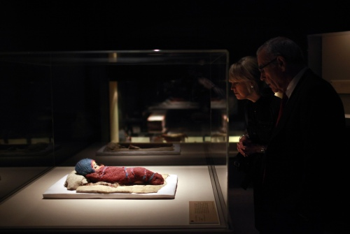 "Edward Roski, right, a board member at the Bowers Museum, looks at a 2,800-year-old infant mummy, Baby Bluebonnet, at the ""Secrets of the Silk Road: Mystery Mummies from China,"" exhibit at the museum in Santa Ana, California. (AP-Yonhap News)"