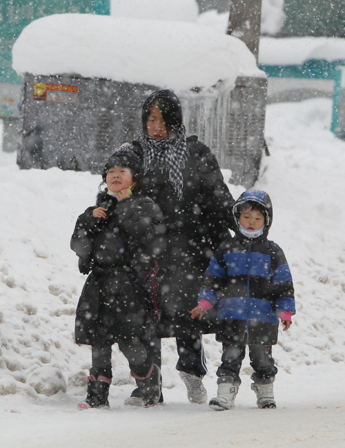 A family waits for public transportation in Gangneung on Monday. (Yonhap News)