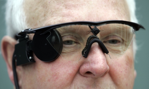 "Eric Selby poses for a photograph with a ""sight"" camera fitted in a pair of glasses, which works in conjunction with an artificial retina implant called the Argus II fitted in his right eye, enabling him to detect light, in Coventry, England.  (AP-Yonhap News)"