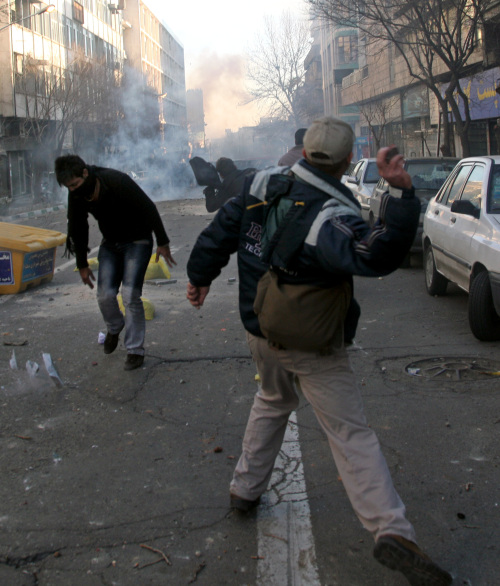 Iranian protesters throw stones at anti-riot police officers during an anti-government protest in Tehran on Monday. (AP-Yonhap News)