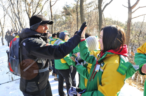 S-Oil CEO Ahmed A. Subey (left) high fives a new employee during a New Year hike in Seoul on Jan. 29. (S-Oil)