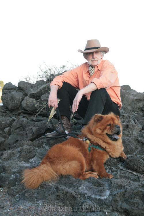 Artist Windsor Joe Innis walks his dog amongst Jeju Island's volcanic rock formations.