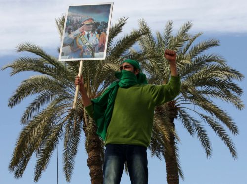 A Libyan pro-government supporter holds a portrait of leader Moamer Kadhafi during a gathering in Tripoli on February 16, 2011 to show support for the veteran leader who seized power in a 1969 coup, as Libya braced for a