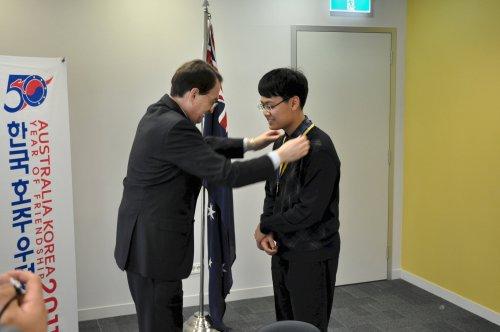 Australia Ambassador Sam Gerovich decorates Chungbuk Science High School student Ryoo Sang-woo. (Yoav Cerralbo/The Korea Herald)