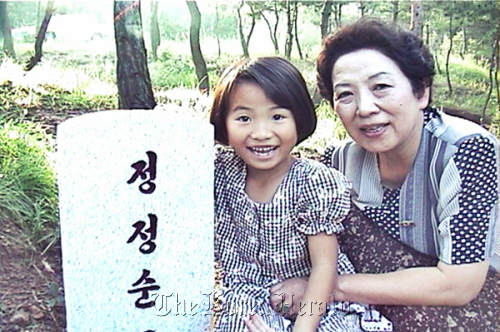 Yang's niece, Son-hwa (left), poses with her grandmother (Yang's mother) at her mother's grave in North Korea in the 1990s. (Kinoeye DMC)