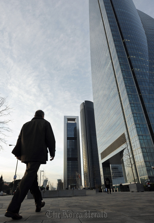 A commuter walks toward the new Cuatro Torres office buildings in Madrid. (Bloomberg)