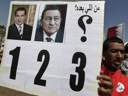 """A Bahraini anti-government protester holds up a banner with pictures of former Tunisian president Zine El Abidine Ben Ali (left) and former Egyptian president Hosni Mubarak (center) and which says in Arabic """"who is next?"""" at the Pearl roundabout in Manama, Bahrain, Sunday. (AP-Yonhap News)"""
