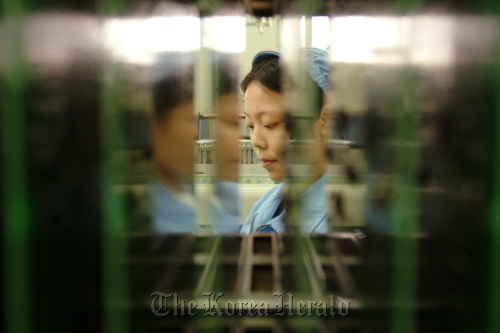 An assembly worker appears between equipment at the Huawei Technologies Company Ltd. factory in Shenzhen, China. (Bloomberg)