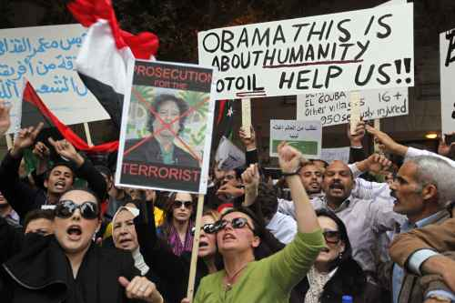Demonstrators call for the ouster of Libyan leader Moammar Gadhafi in front of the Libyan Embassy in Cairo on Sunday. (AP-Yonhap News)