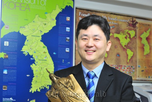 Park Gi-tae, president of Voluntary Agency Network of Korea, poses against a wall showing a Korean map in the VANK office in Seoul. (Kim Myung-sub/The Korea Herald)