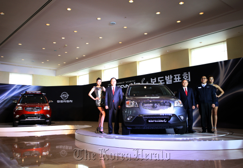 Ssangyong Motor Co. court receivership managers Lee Yoo-il (second from left) and Park Young-tae (third from right) pose with the Korando C at the launch event in Jeju on Tuesday. (Ssangyong Motor Co.)
