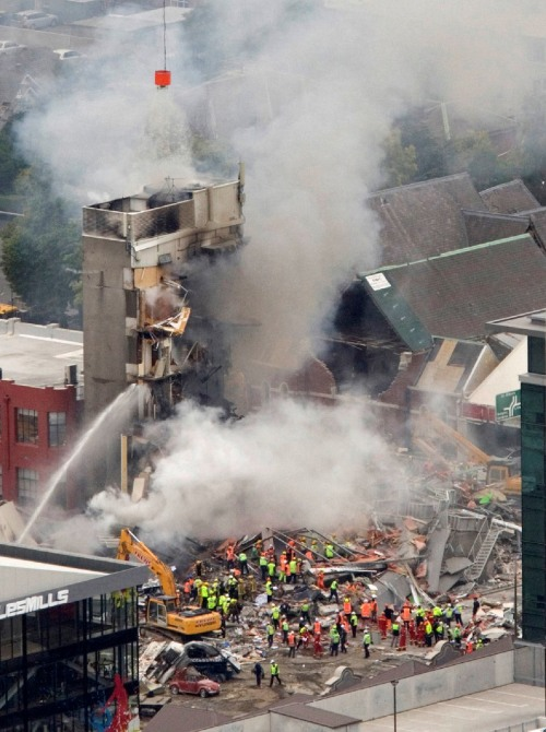 Rescue workers work to extinguish a fire at a collapsed building in central Christchurch, New Zealand, Tuesday, Feb. 22, 2011. A powerful earthquake collapsed buildings at the height of a busy workday Tuesday, killing and trapping dozens in one of the country's worst natural disasters. (AP-Yonhap)