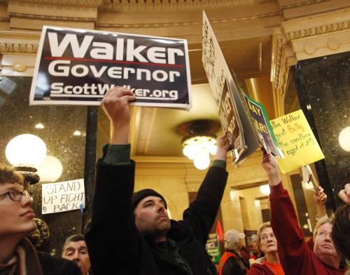 A supporter of Wisconsin Gov. Scott Walker walks among hundreds of protesters inside the state Capitol Tuesday, in Madison, Wisconsin. (AP-Yonhap News)