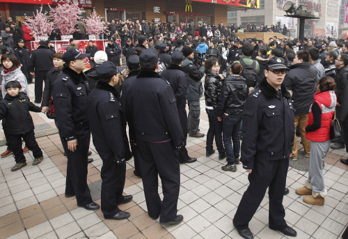"""Police officers stand watching people gathering in front of a McDonald's restaurant which was a planned protest site for """"Jasmine Revolution"""" in Beijing. (AP-Yonhap News)"""