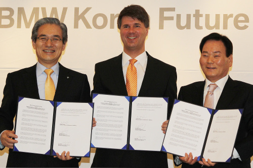 BMW's human resources director Harald Kruger (center), BMW Korea president Kim Hyo-joon (left) and head of BMW dealers' association Park In-ju hold up the agreement to set up the BMW Korea Future Fund in Seoul on Thursday. (Yonhap News)