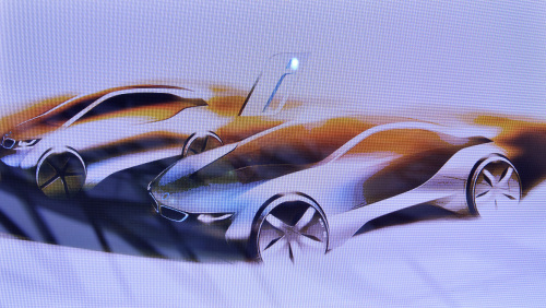 An artist's illustration of the new Bayerische Motoren Werke AG (BMW) i3, left, and i8 automobiles are displayed during the launch of the new