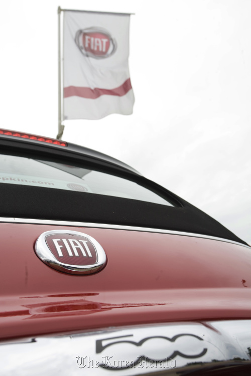 A Fiat flag flies above a Fiat automobile. (Bloomberg)