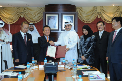 Hyundai E&C CEO Kim Joong-kyum (third from left) and Nasser Ali Al-Mawlawi (third from right), acting general manager of Qatar's Public Works Authority, shake hands after signing a contract in December. (Hyundai E&C)