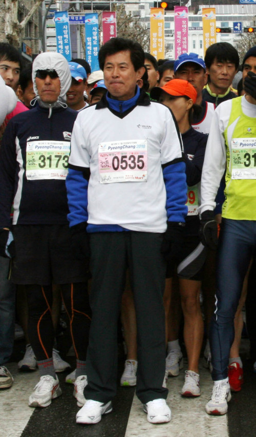 Choi Moon-soon (upper photo) and Eom Ki-young, both former presidents of MBC, attend a marathon in Chuncheon, Gangwon Province, Tuesday. They are running for the province's gubernatorial post in the upcoming by-elections on the tickets of the main opposition Democratic Party and the ruling Grand National Party, respectively. (Yonhap News)
