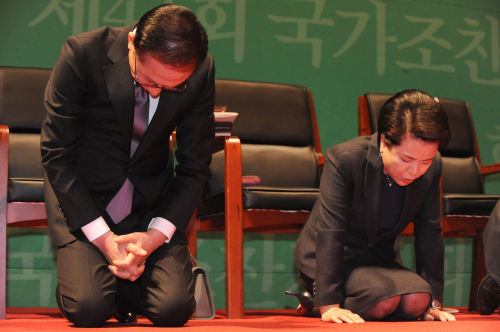 President Lee Myung-bak and first lady Kim Yoon-ok pray on their knees during the national prayer breakfast in Seoul on Thursday. Lee, a Protestant elder, has faced criticism from some Christian leaders over the government's Islamic finance plan.(Chung Hee-cho/The Korea Herald)