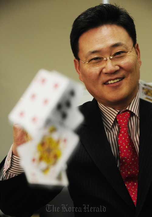 Former world poker champion Jimmy Cha scatters a deck of cards at his Casino International Group office in Seoul. (Park Hae-mook/The Korea Herald)