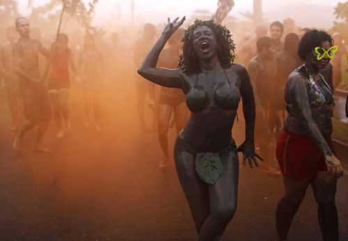 A woman dances amid orange smoke during the 'Bloco da Lama', or Mud Block carnival group parade in Paraty, Brazil, Saturday, March 5, 2011.(AP-Yonhap News)