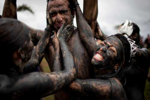 Members of the the 'Bloco da Lama', or Mud Block carnival group, cover a man in mud during carnival celebrations in Paraty, Brazil, Saturday, March 5, 2011. (AP-Yonhap News)