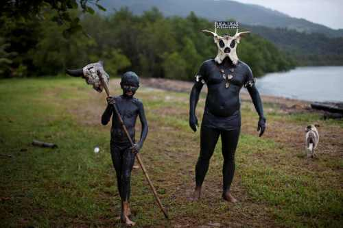 Revelers of the 'Bloco da Lama', or Mud Block, carnival group, walk covered in mud before a carnival parade in Paraty, Brazil, Saturday, March 5, 2011. (AP-Yonhap News)