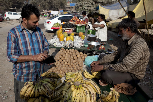 A customer looks at a fruit stall in New Delhi, India. (Bloomerg)