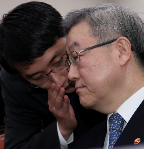 Foreign Minister Kim Sung-hwan listens to an aide during a parliamentary session convened Wednesday to deal with the scandal involving Deng Xinming, a Chinese woman, and South Korean diplomats in Shanghai. (Yonhap News)