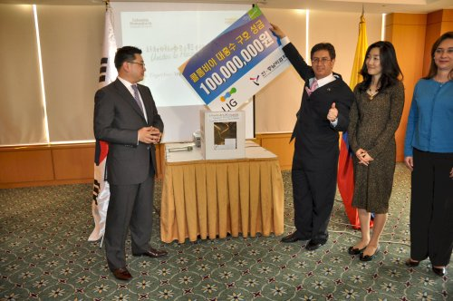 Colombia Charge d'Affaires Manuel Solano (second from right) gives a thumb up to a 100 million won check donated by Vice Chair of LIG Korea Koo Bon-sang (left). (Yoav Cerralbo/The Korea Herald)