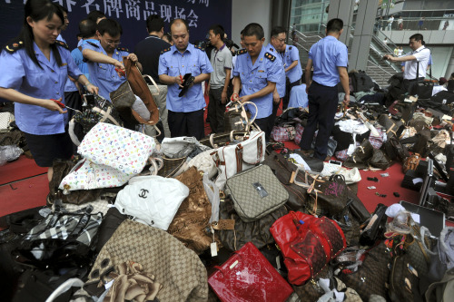 Chinese business administration officers cut fake luxury branded handbags during a mass elimination of counterfeit products in southwest China's Chongqing city. (AP-Yonhap News)