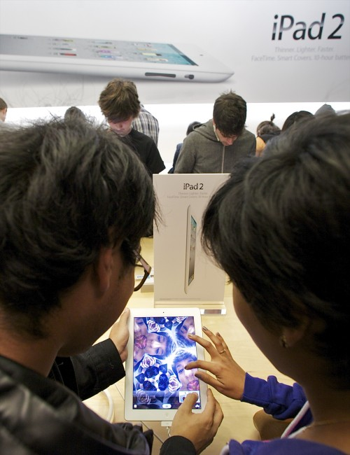 Shoppers try the front camera of the new iPad 2 at The Grove Apple store in Los Angeles on Friday. (AP-Yonhap News)