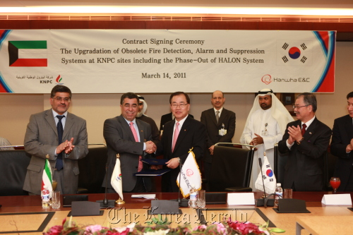 Hanwha E&C CEO Kim Hyung-chung and Kuwait National Petroleum Co.'s Asaad Ahmad Al-Saad (second from left) shake hands after signing a contract in Safat, Kuwait, Monday. (Hanwha Engineering and Construction Co.)