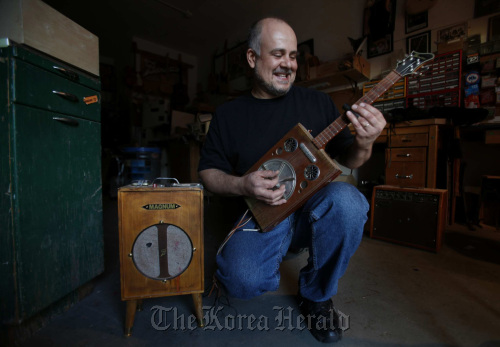 Guitar builder Matthew (Matty) Baratto with one of his custom Cigfiddle cigar-box guitars and his handmade amp inside his North Holllywood shop. (MCT)