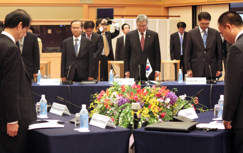 Foreign Minister Kim Sung-hwan (center) and other officials pay silent tribute to Japan's quake victims at the start of a meeting between top diplomats from South Korea, China and Japan in Kyoto on Saturday. (Yonhap News)
