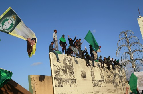Supporters of Libyan leader Moammar Gadhafi wave flags as they anticipate his arrival at his Bab Al Azizia compound in Tripoli, Libya, Saturday. (AP-Yonhap News)