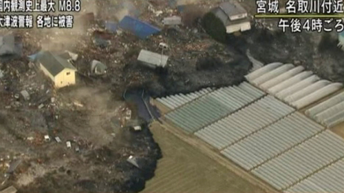 In this video image taken from Japan's NHK TV, a tsunami surge carrying debris sweeps between houses to reach poly tunnels on farmland near Sendai in Miyagi Prefecture Japan on March 11. (AP-Yonhap News)