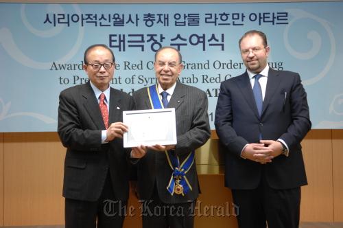 Korean Red Cross President Yoo Chong-ha (left) awards the Grand Order Taegug to President of the Syrian Arab Red Crescent Abdul Rahman Attar on Monday. (Korean Red Cross)
