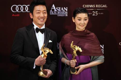 Actor Ha Jung-woo of South Korea and actress Xu Fan of China pose with their trophies after taking Best Actor and Best Actress awards at the Asian Film Awards in Hong Kong on Monday. (AFP-Yonhap News)