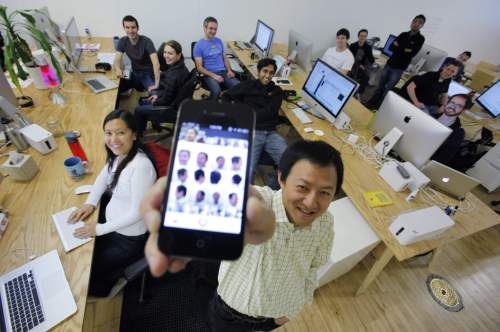 Color co-founder Bill Nguyen holds up his Apple iPhone with photos of himself using the Color application as he poses with staff members at the company's offices in Palo Alto, California. (AP-Yonhap News)