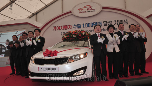 Kia Motors Corp. and government officials including Kia vice chairman Lee Hyung-keun (fifth from right) and Gyeonggi Province Governor Kim Moon-soo (fifth from left) pose with the 10 millionth Kia vehicle to be shipped abroad at the Pyeongtaek Port in Gyeonggi Province on Thursday. (Chung Hee-cho/The Korea Herald)