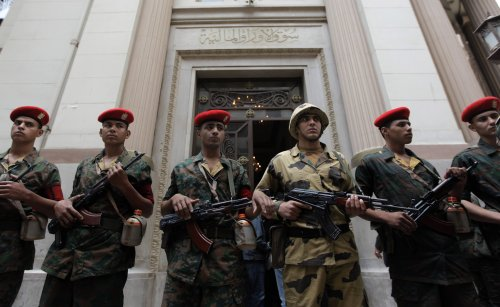 Egyptian army soldiers guard the entrance of Egypt's stock exchange, background, during it's reopening session after a nearly two-month closure, in Cairo. (AP-Yonhap News)