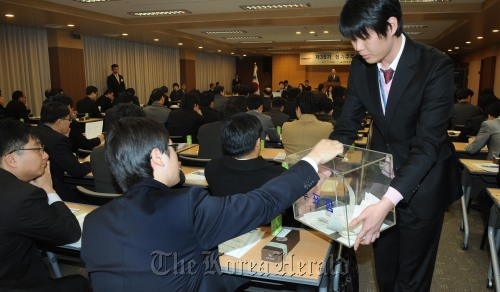 A Hyundai Merchant Marine shareholder casts a ballot on a proposal to increase the preferred stock sales limit at a shareholders meeting Friday. (Park Hyun-koo/The Korea Herald)