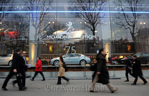Pedestrians pass the PSA Peugeot Citroen company headquarters in Paris. (Bloomberg)