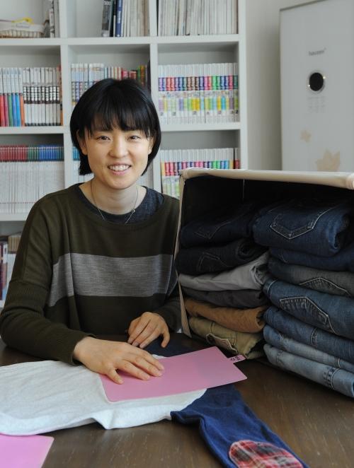 Shim Hyun-joo demonstrates how to use a folding guide to fold T-shirts. (Lee Sang-sub/ The Korea Herald)